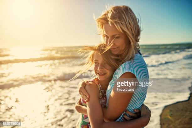 Mother and daughter embracing at the beach