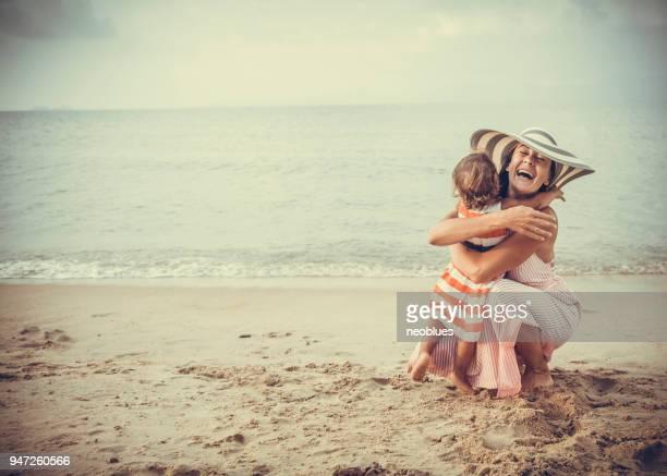 Moeder en dochter omarmen op het strand