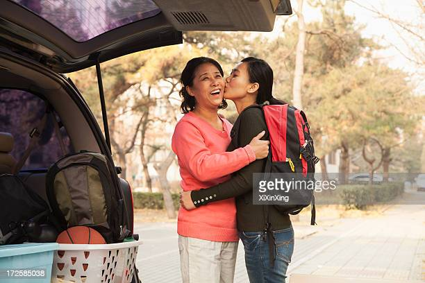 mother and daughter embracing behind car on college campus - tag 1 stock-fotos und bilder