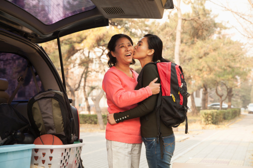 Mother and daughter embracing behind car on college campus 183577046