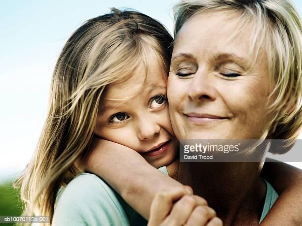 Mother and daughter (6-7) embracing, close-up