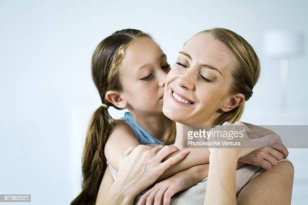 mother and daughter embracing, girl kissing woman's cheek - cheek stock pictures, royalty-free photos & images
