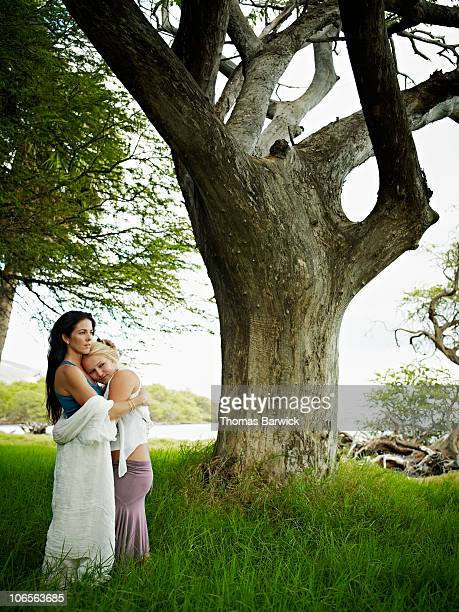 Mother and daughter embracing in grass field