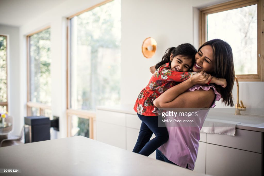 Mother and daughter embracing in kitchen : Stock Photo