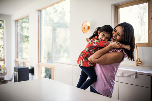 Mother and daughter embracing in kitchen - gettyimageskorea