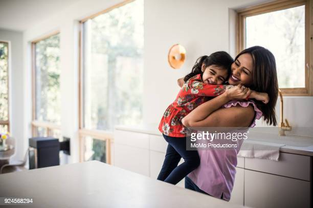 mother and daughter embracing in kitchen - één ouder stockfoto's en -beelden