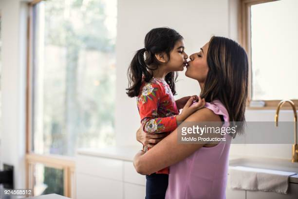 mother and daughter embracing in kitchen - indian girl kissing stock photos and pictures