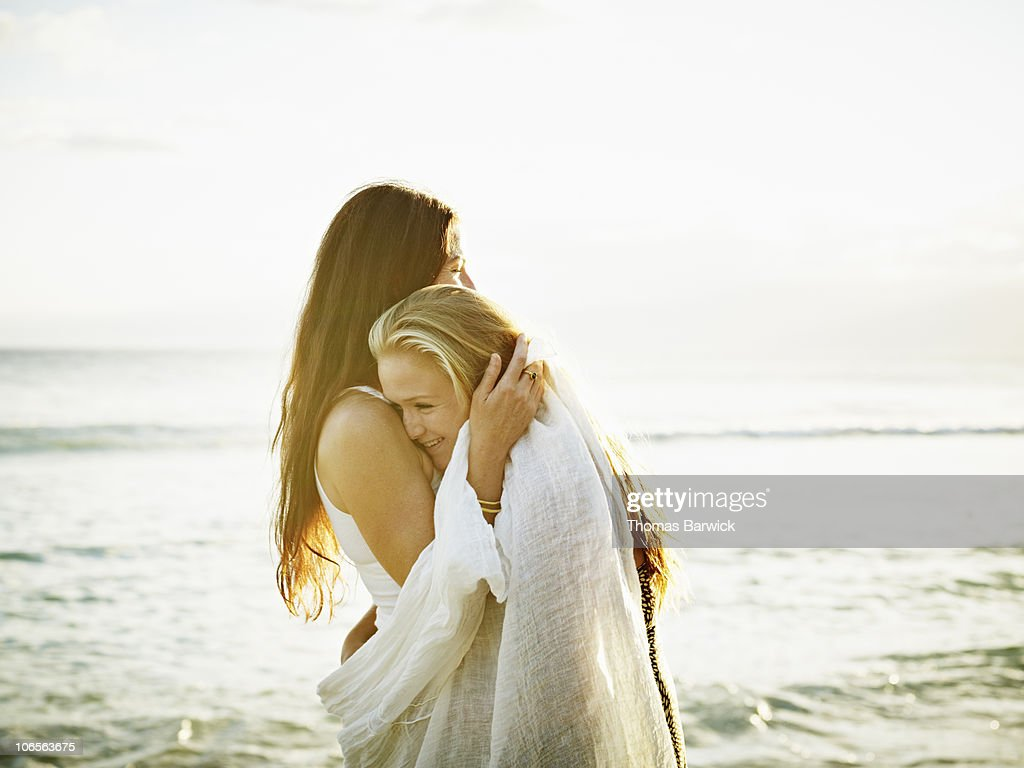 Mother and daughter embracing on beach at sunset : Stock Photo