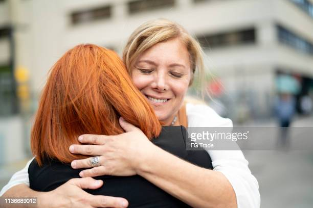 mother and daughter embracing on the city - reconciliation stock pictures, royalty-free photos & images