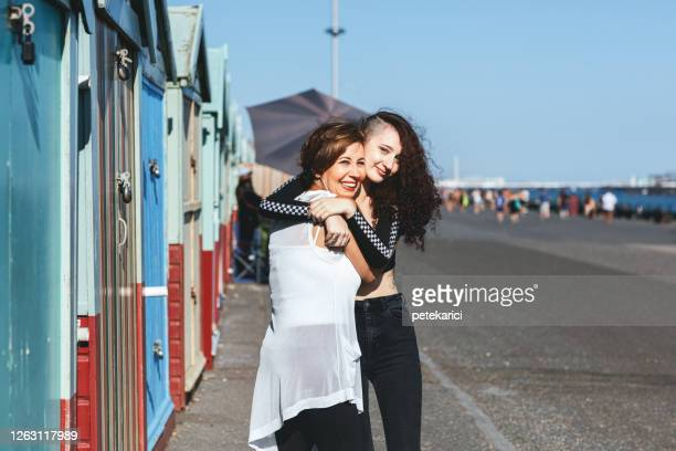 mother and daughter embracing on the city - showus stock pictures, royalty-free photos & images