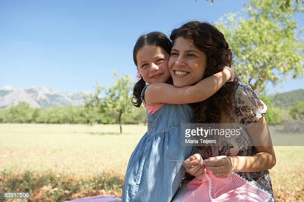 mother and daughter embracing outdoors