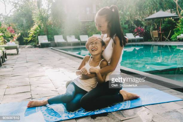 Mother and daughter  embracing sitting on yoga mat  near  swimming pool