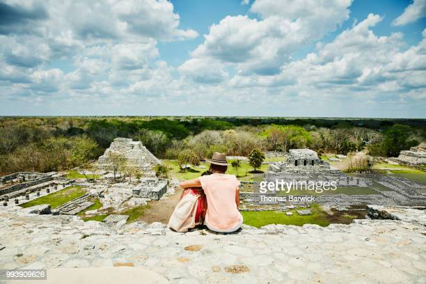 Mother and daughter embracing while sitting at top of ruins in Mayapan and taking in view