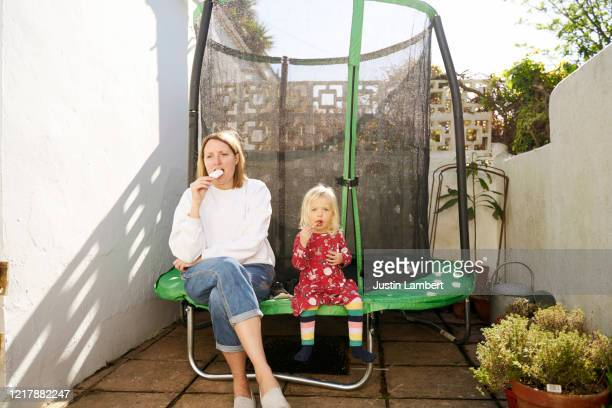 mother and daughter enjoy an ice cream after erecting a trampoline in the back yard - moment of silence stock pictures, royalty-free photos & images