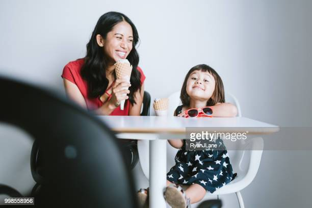 mother and daughter enjoy an ice cream cone together - filipino family eating stock pictures, royalty-free photos & images