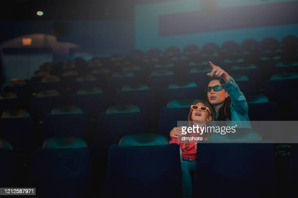 mother and daughter enjoying a movie - dark blue stock pictures, royalty-free photos & images