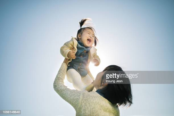 mother and daughter enjoying day out - asian baby stockfoto's en -beelden