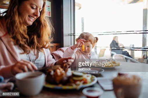 Mother and Daughter Enjoying Food at a Beach Cafe