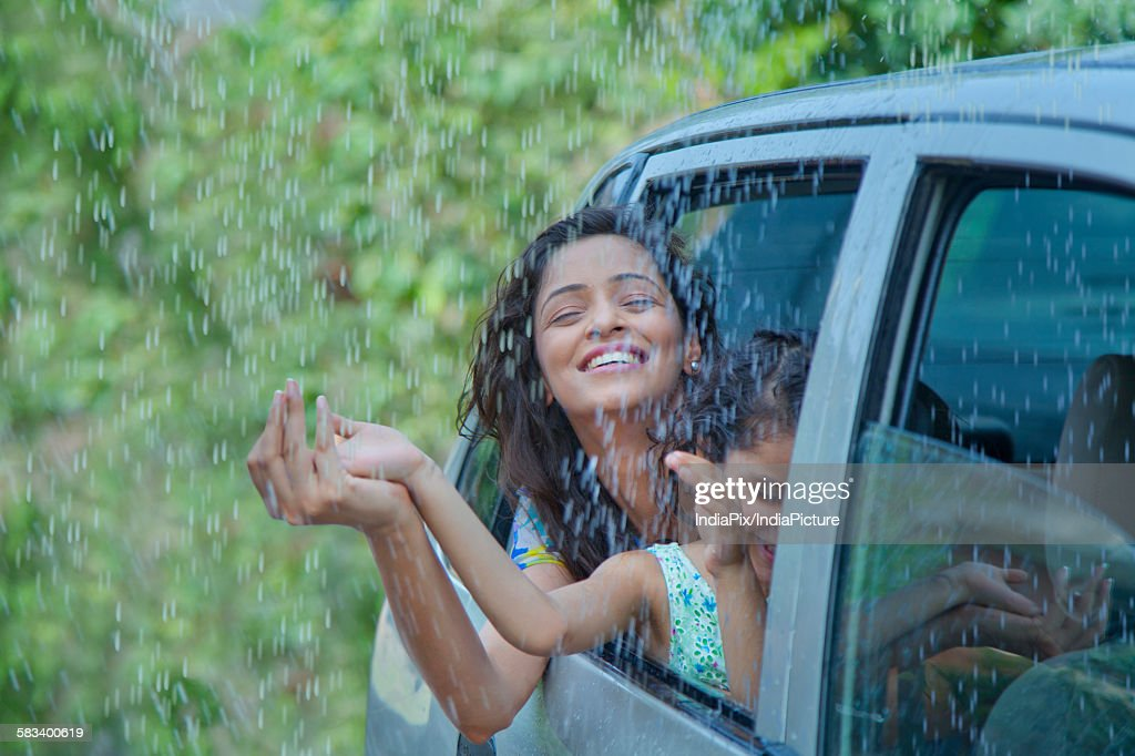 Mother and daughter enjoying the rain : Stock Photo
