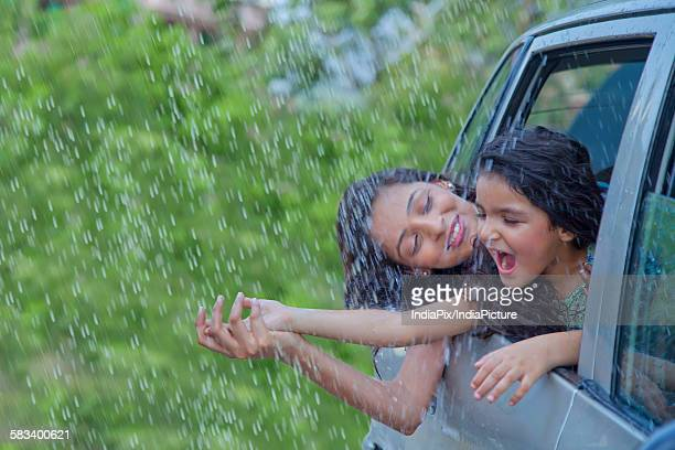 Mother and daughter enjoying the rain