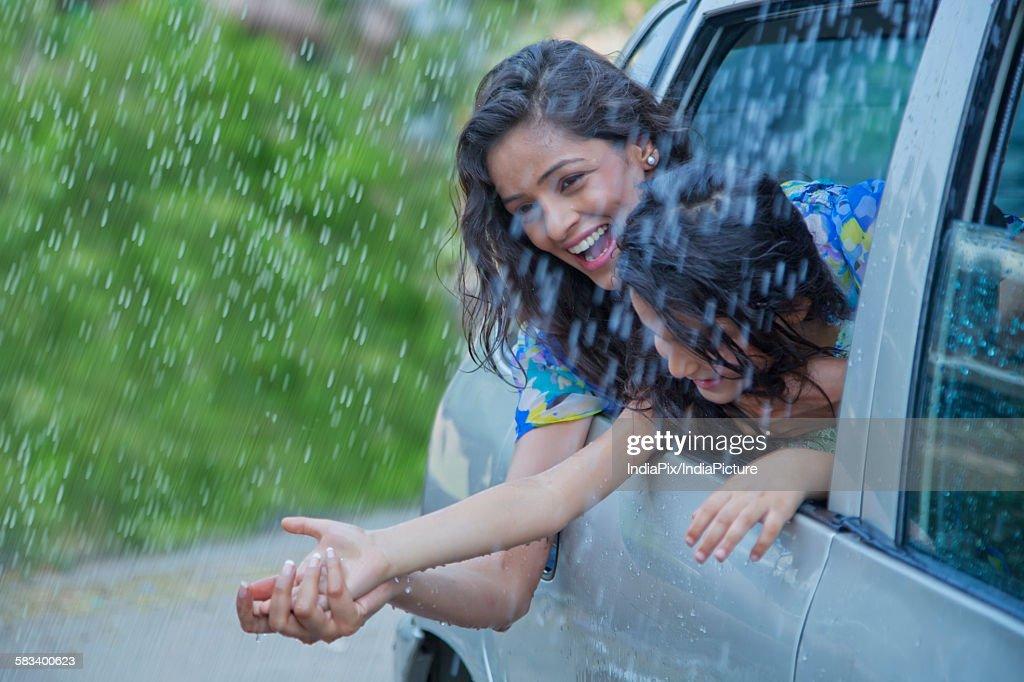 Mother and daughter enjoying the rain : Stock Photo