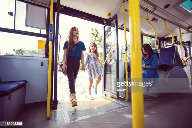 mutter und tochter betreten gemeinsam bus - eintreten stock-fotos und bilder
