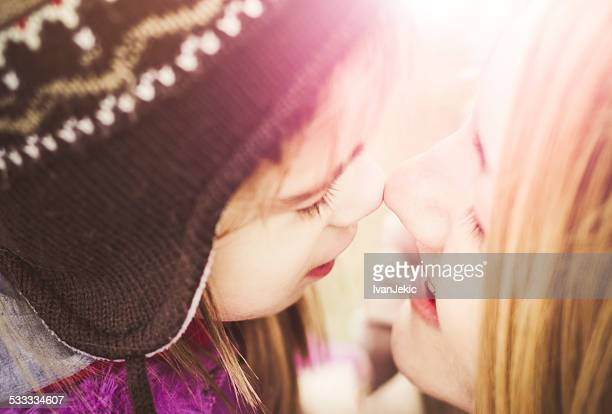 Mother and daughter eskimo kissing closeup