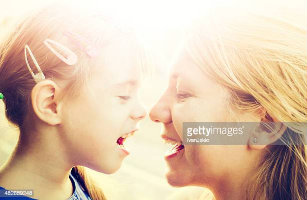 Mother and daughter eskimo kissing outdoors at sunset