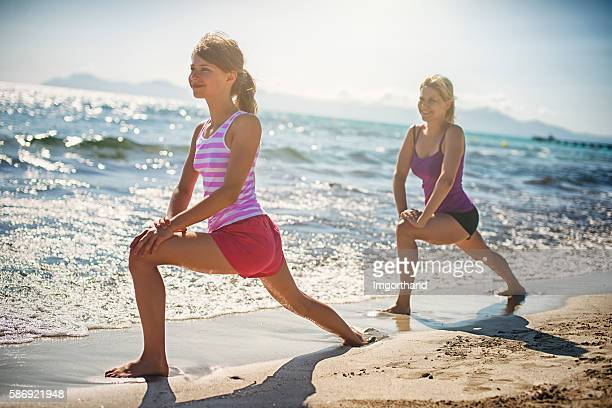 Mother and daughter exercising on beach