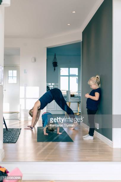 mother and daughter exercising on mat while girl standing in living room at home - エクササイズルーム ストックフォトと画像
