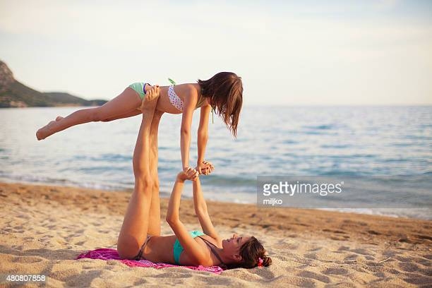 Mother and daughter exercising on the beach