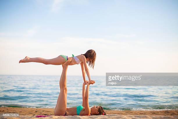 Mère et fille faisant des exercices sur la plage