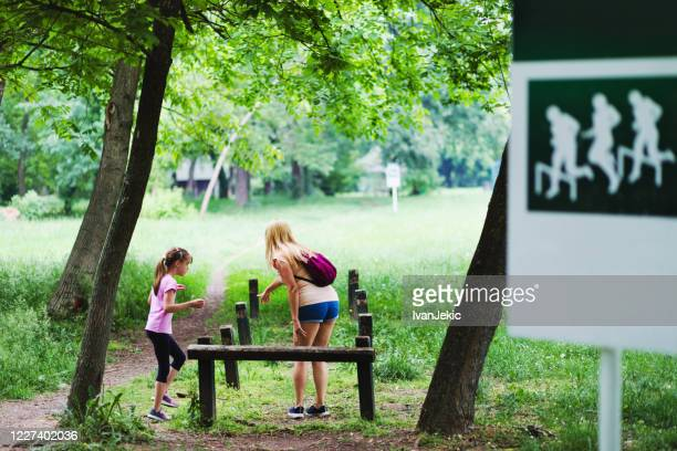 mother and daughter exercising outdoors - ivanjekic stock pictures, royalty-free photos & images