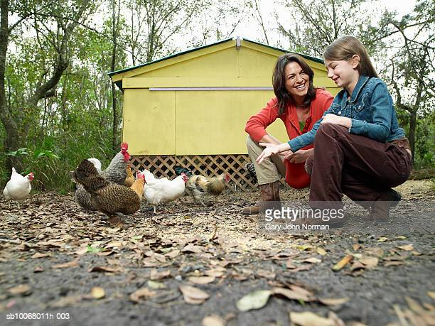 Mother and daughter (6-7) feeding chickens