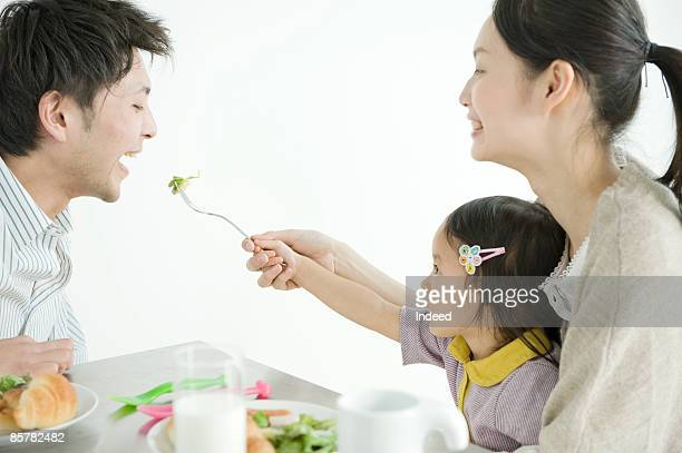 Mother and daughter feeding food to father