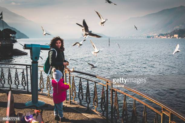 Mother and daughter feeding gulls on lake Como at winter