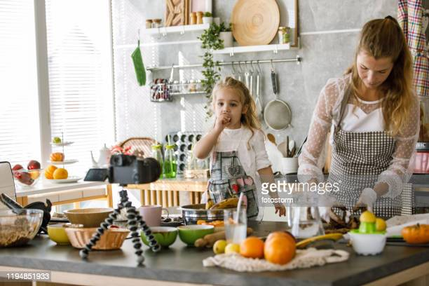 mère et descendant filmant un tutoriel vidéo sur la façon de faire des biscuits végétaliens crus - influenceur photos et images de collection