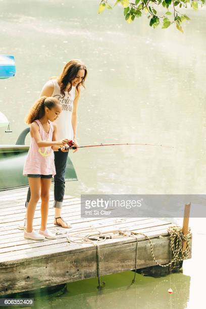Mother and daughter fishing in lake