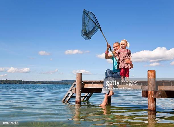 mother and daughter fishing with net - fish love stockfoto's en -beelden