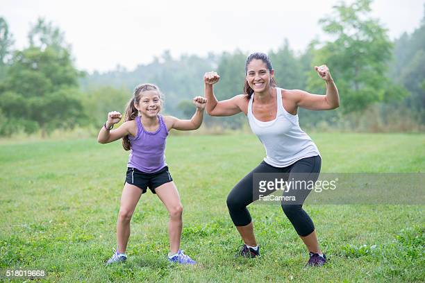 mother and daughter flexing - spieren spannen stockfoto's en -beelden