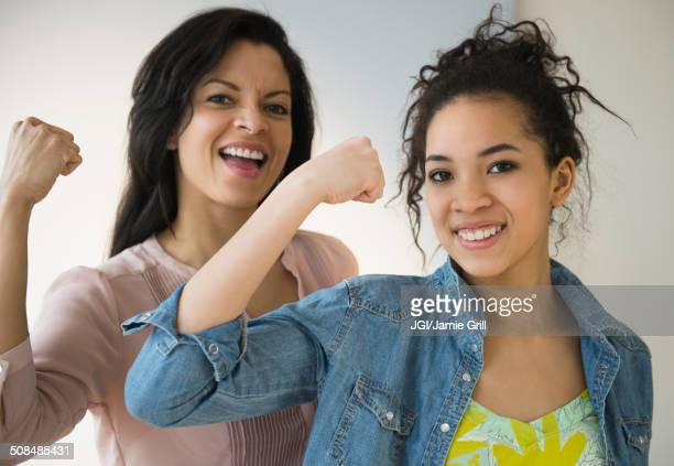 Mother and daughter flexing their muscles