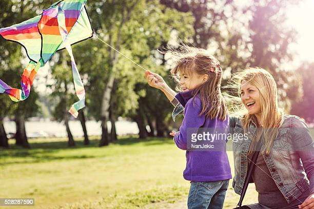 Mother and daughter flying kite in nature