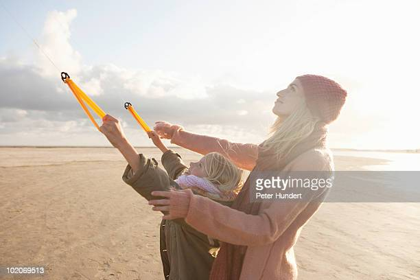 Mother and daughter flying kite on beach