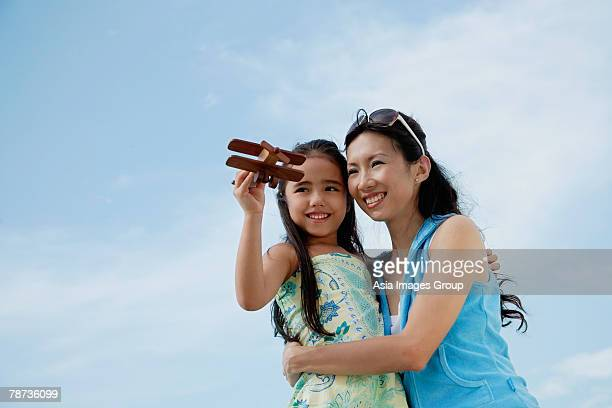 Mother and daughter flying wooden airplane, mother holding daughter