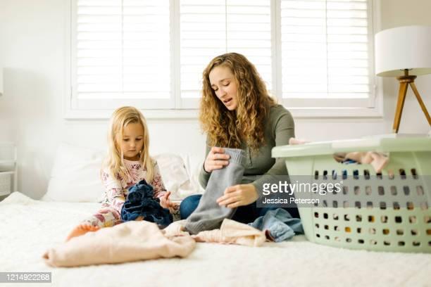 mother and daughter folding laundry on bed - haushaltsaufgabe stock-fotos und bilder