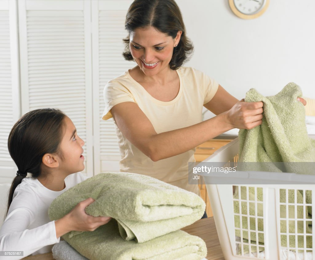 Mother and daughter folding laundry together : Stock Photo