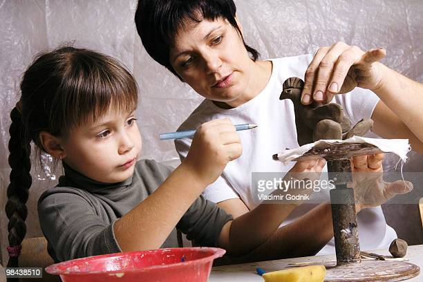 mother and daughter forming sculpture out of clay together