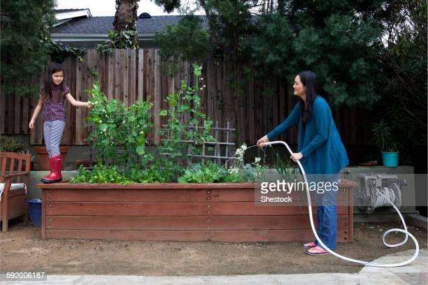 Mother and daughter gardening in backyard