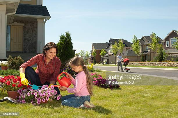 mother and daughter gardening while father walks with baby - borough district type stock pictures, royalty-free photos & images
