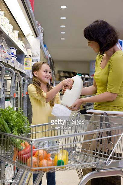 Mother and daughter getting milk in supermarket